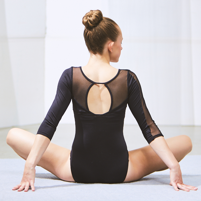 Seated young dancer in leotard facing away