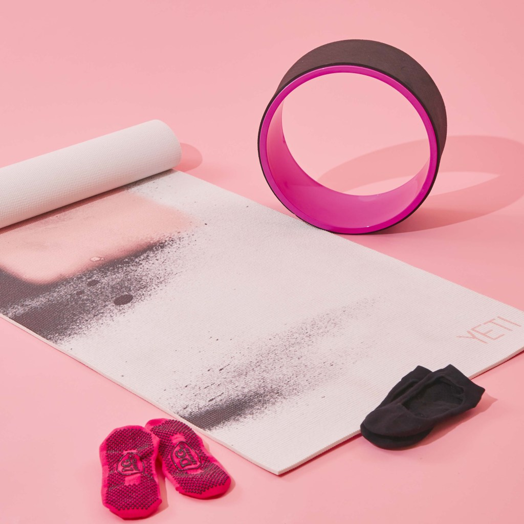 Yoga mat and accessories against a pink background