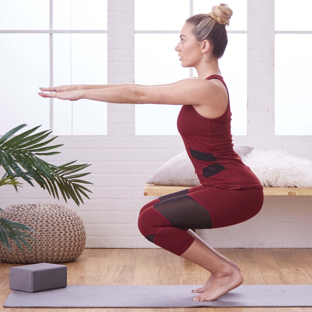 Woman practicing yoga with block and plant