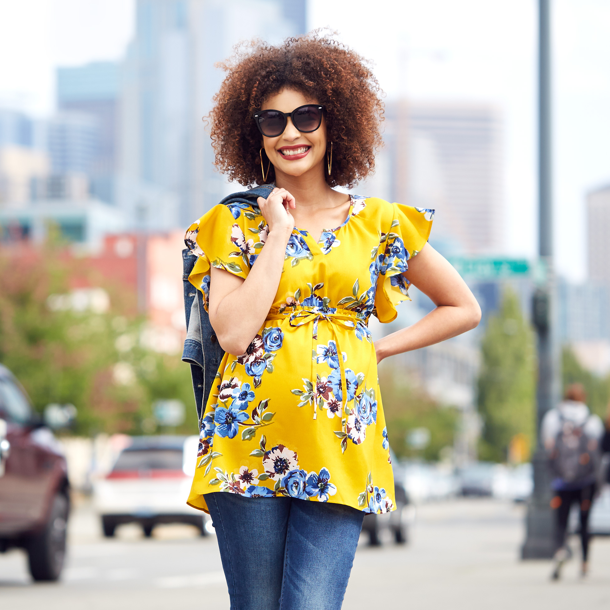 Woman wearing yellow floroal flutter-sleeve maternity top