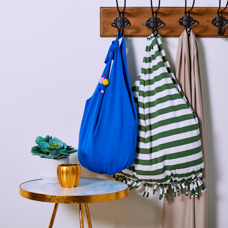 two t-shirt tote bags hanging on hooks