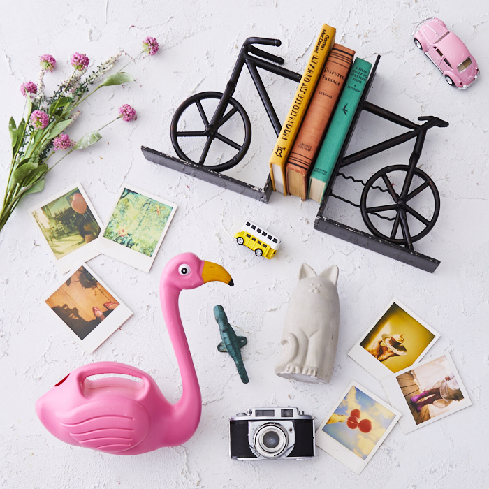 Display of pink blossoms, plastic flamingo, polaroid photos, bicycle bookends and assorted small toys