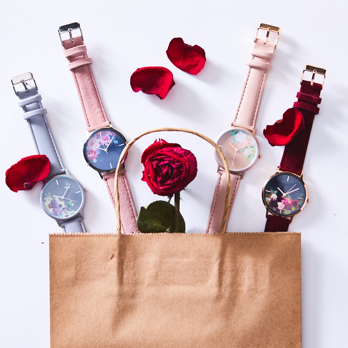 Shopping bag with pink and blue watches and rose petals