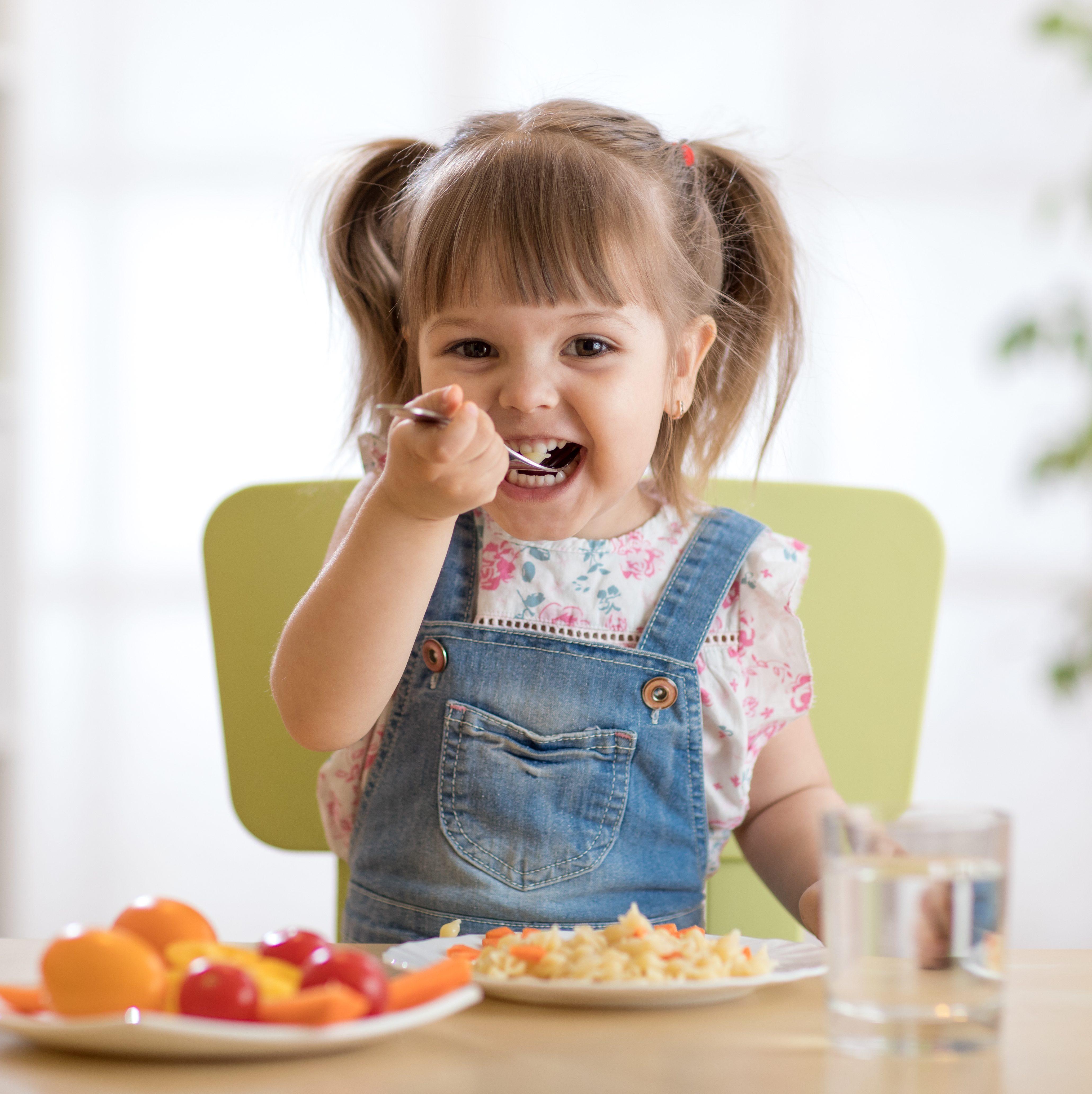 little girl eating healthy food in kindergarten