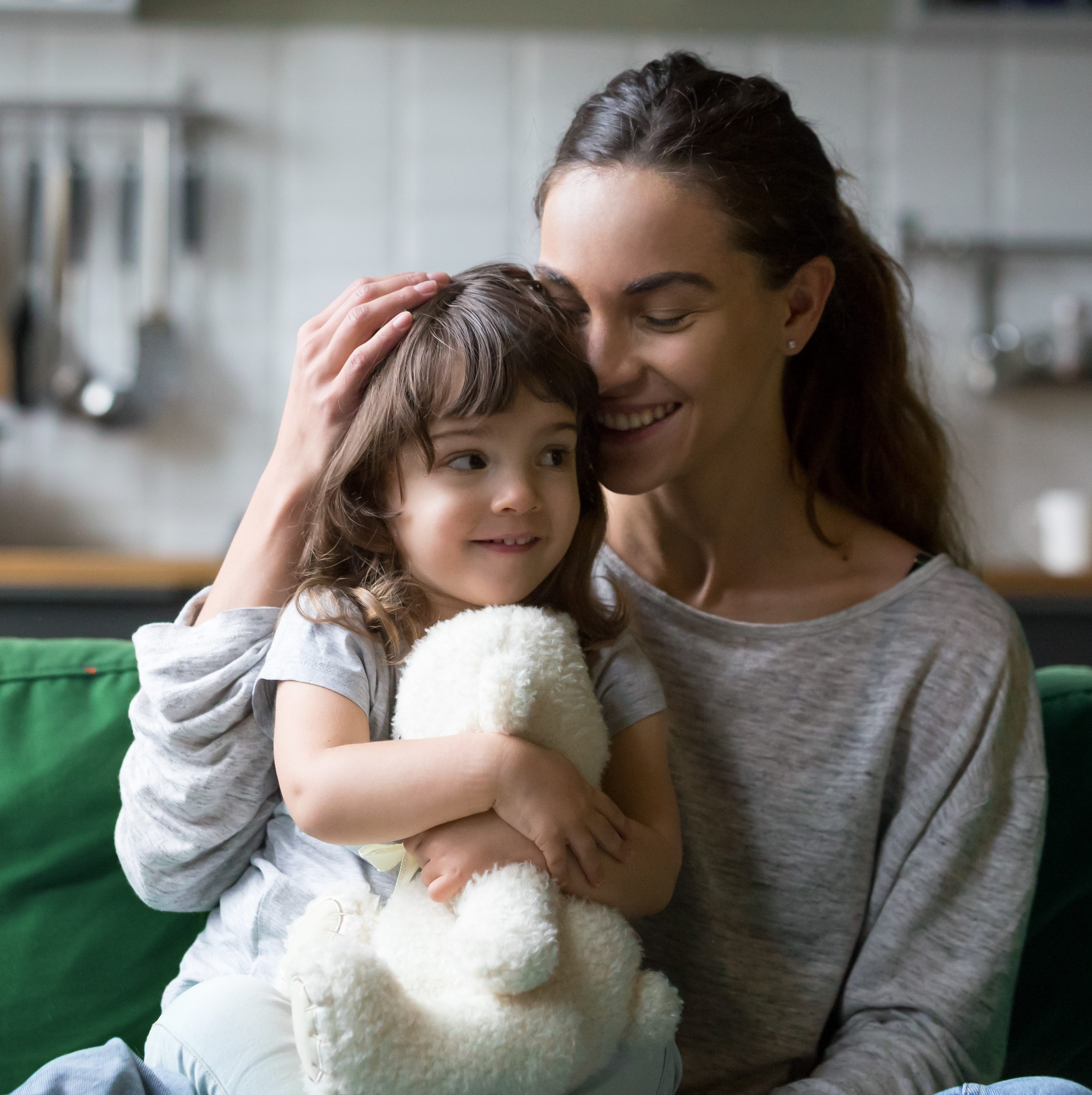 Happy single mother hugging daughter