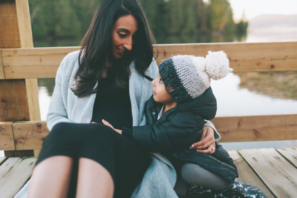Mother hugging child with beanie on a bridge