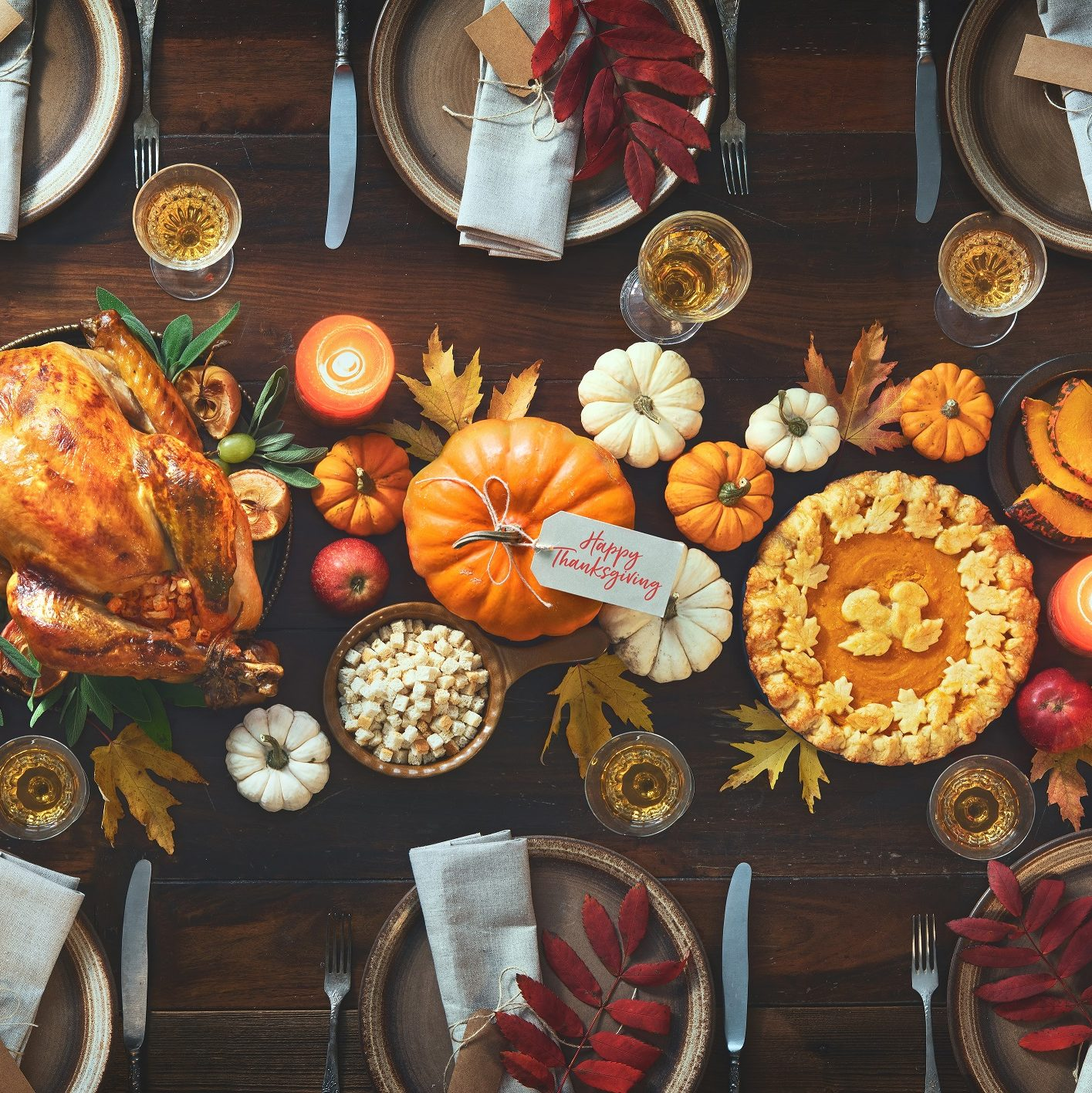 Decorated Thanksgiving table with turkey, pumpkins, leaves and napkins.