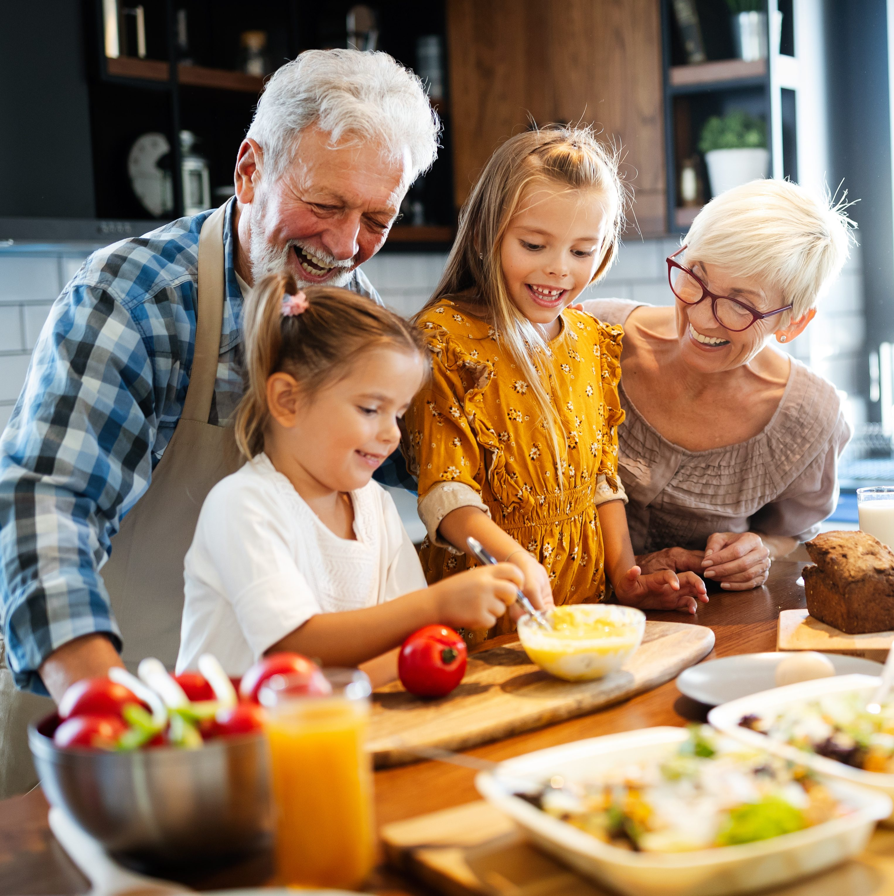 couple having breakfast with their grandchildren at home