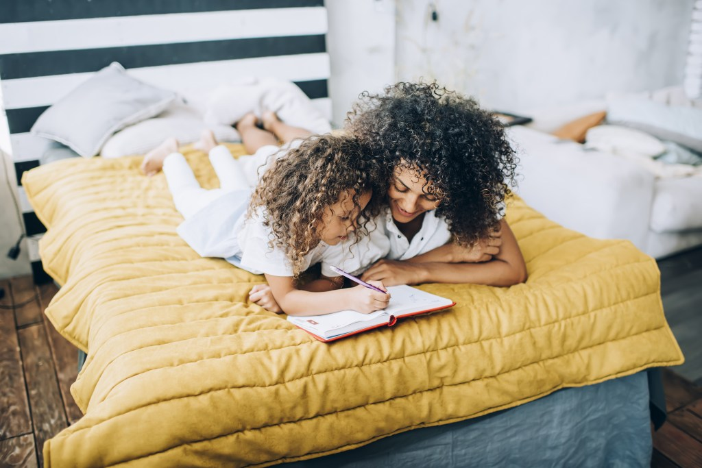 Mother and child journaling on bed