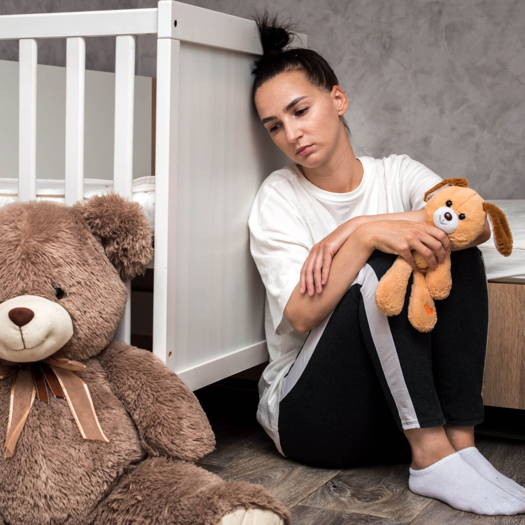 Woman sitting next to crib looking anxious - potentially because of postpartum despression