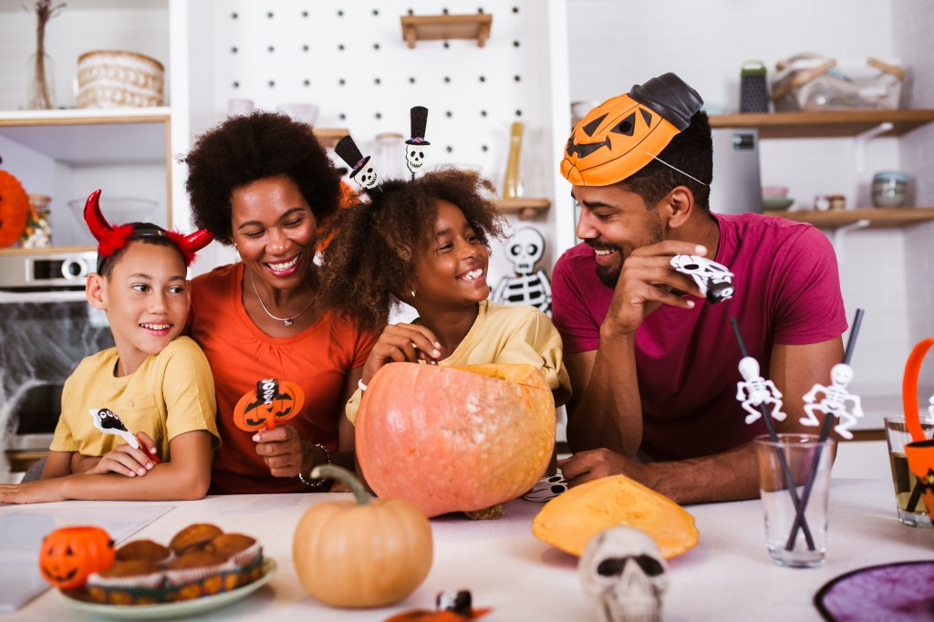 family enjoying Halloween at home in costumes