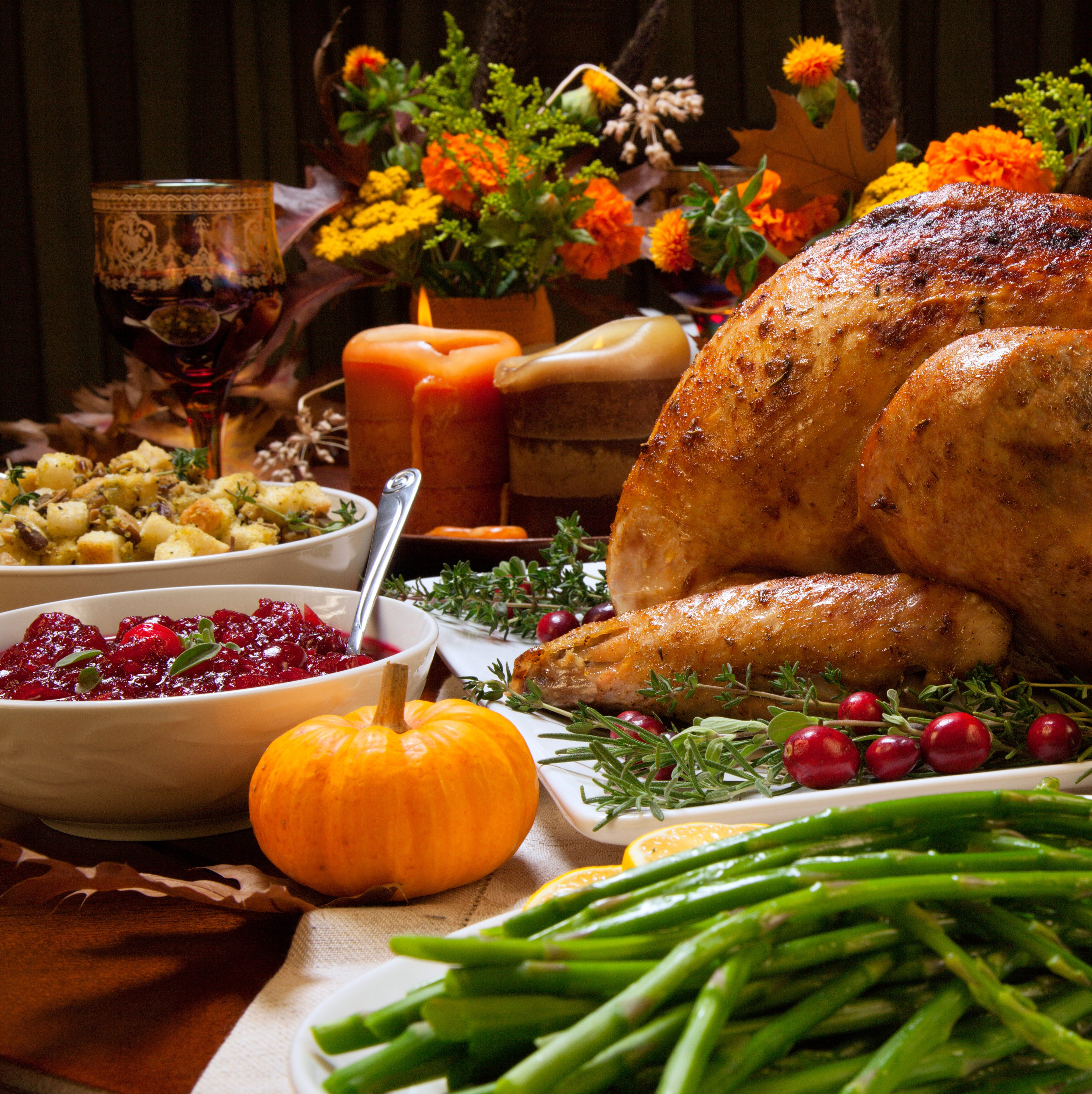 Roasted turkey garnished with cranberries on a rustic style table decorated with pumpkins, gourds, asparagus, brussel sprouts, baked vegetables, pie, flowers, and candles.