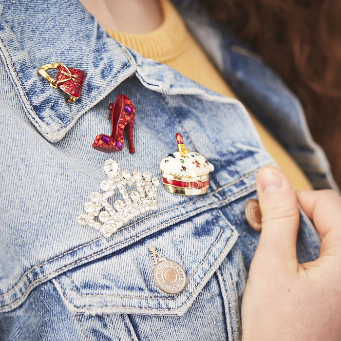 Denim jacket lapel with stiletto, cupcake and crown rhinestone pins