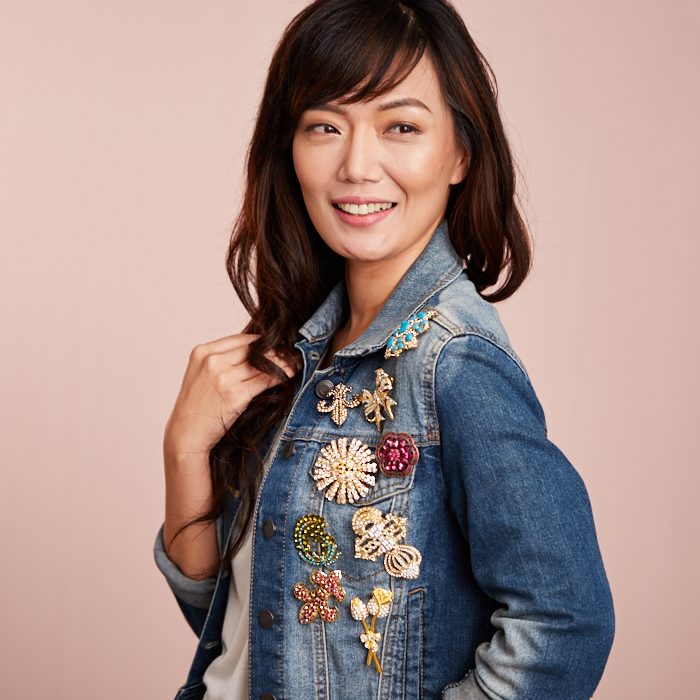 Woman wearing distressed denim jacket decorated with floral brooches