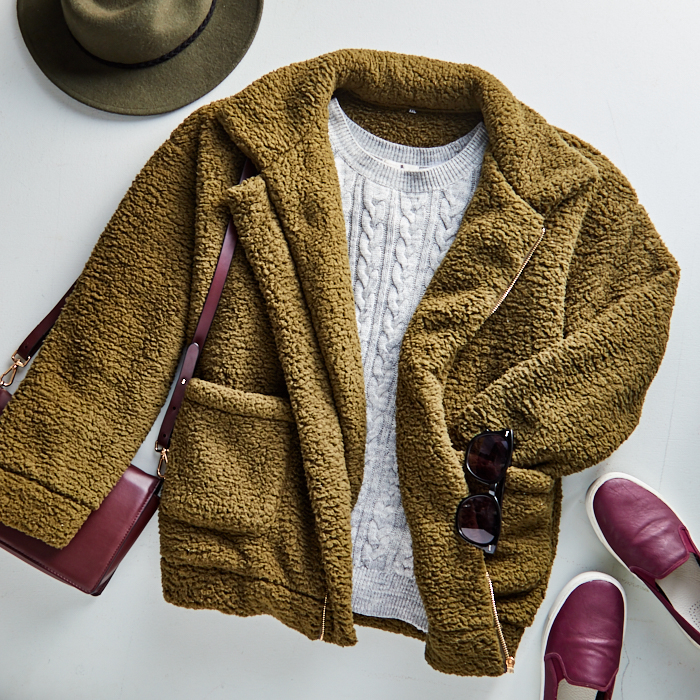 olive green teddy jacket flatlay over light gray cable crewneck sweater and burgundy loafers