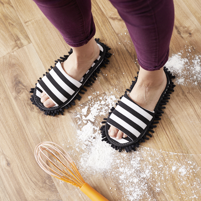 Feet wearing flip-flops with dust-cloth soles, sliding over spilled flour in kitchen floor