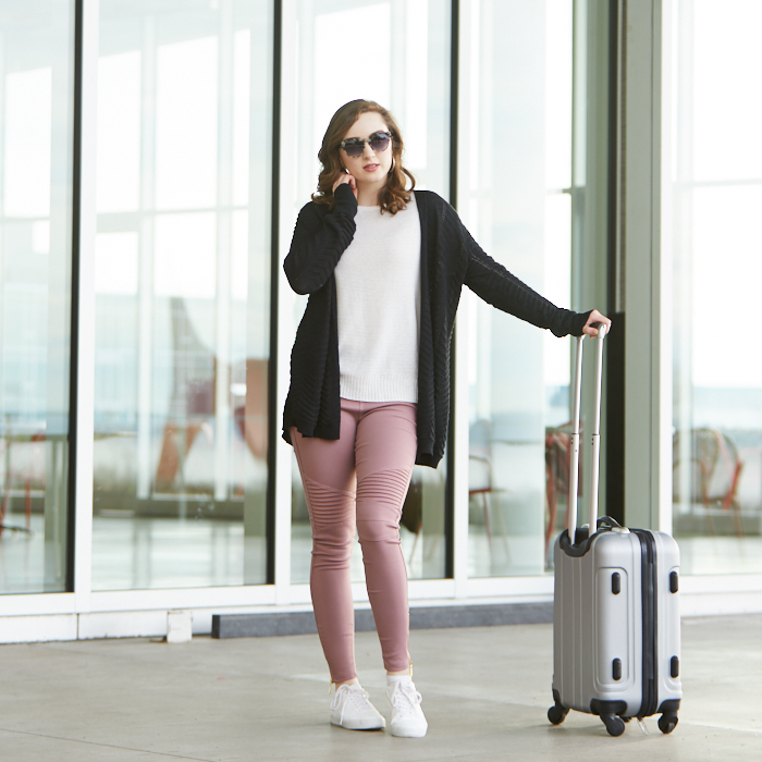 College student wearing sunglassed standing outside airport with suitcase