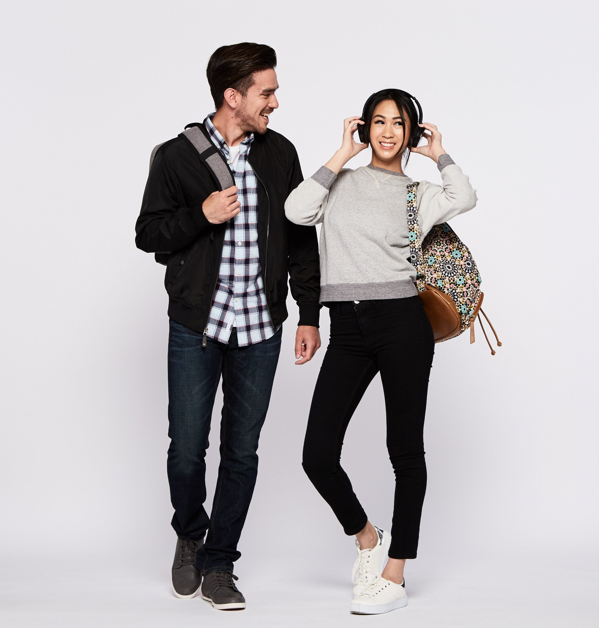 Cheerful college guy and girl carrying backpacks
