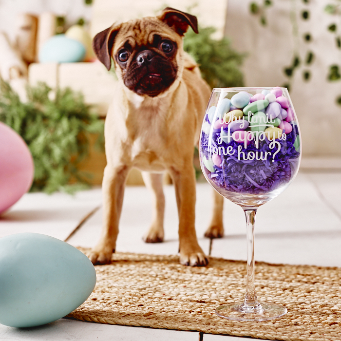 """Pug puppy beside almond-filled wine glass etched with """"Why Limit Happy to One Hour"""""""