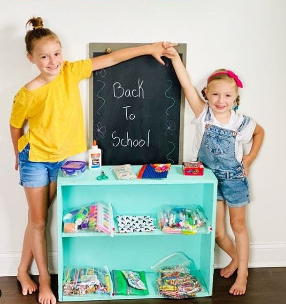 two sisters with back-to-school sign