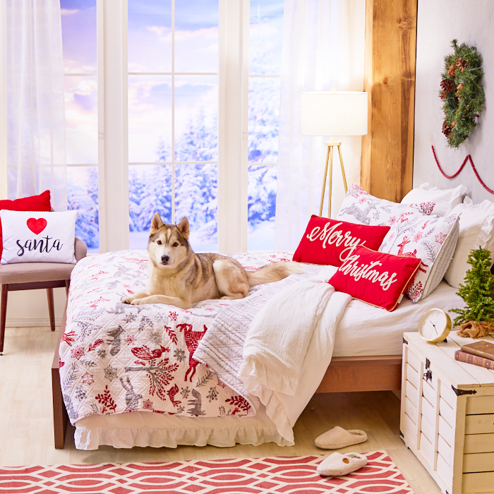 Guest room with holiday pillows and dog resting on bed