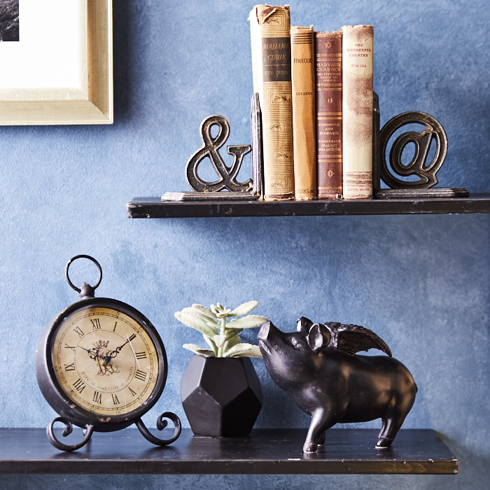 Vintage-inspired staging with brass winged pig, old books and windup clock