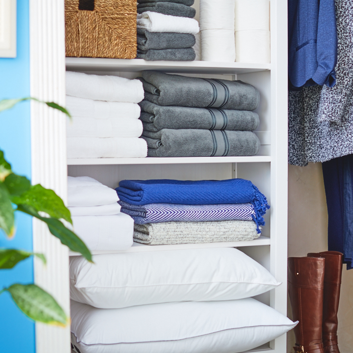 guest room and linen closet with towels, clothing and pillows