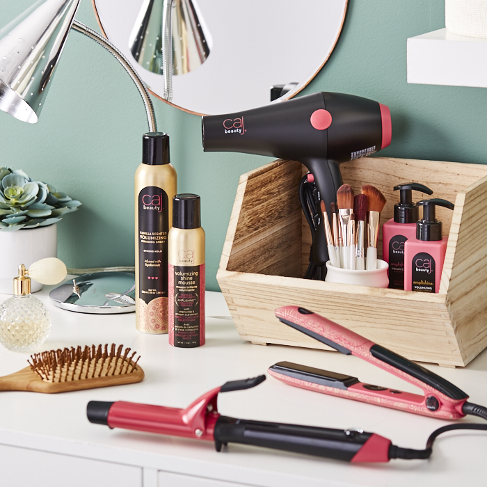Assortment of hair products and tools in pink, black and gold tones