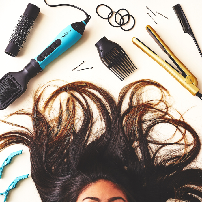 Long-haired model surrounded by curling iron, brushes, styling tools