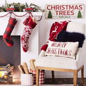 fireplace with Christmas stockings, pine bough decoration and holiday pillows