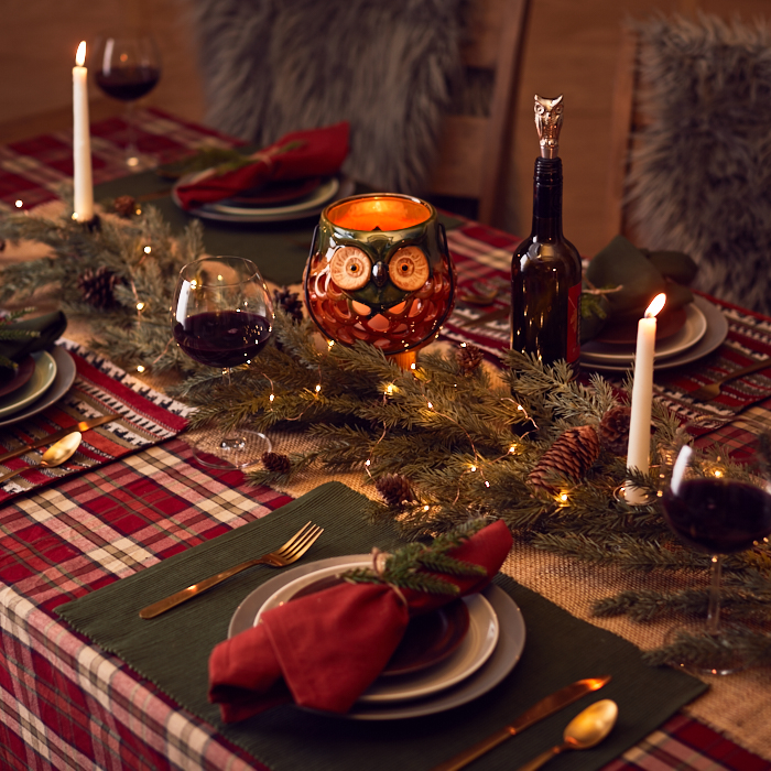 Get festive with a red plaid holiday table cloth with green mats, pine boughs and red owl candle