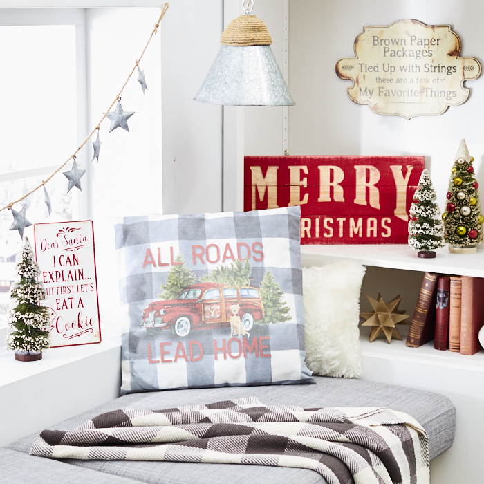 A corner window decorated with silver star garland, holiday pillow and Merry Christmas signs looks sleek and cheery