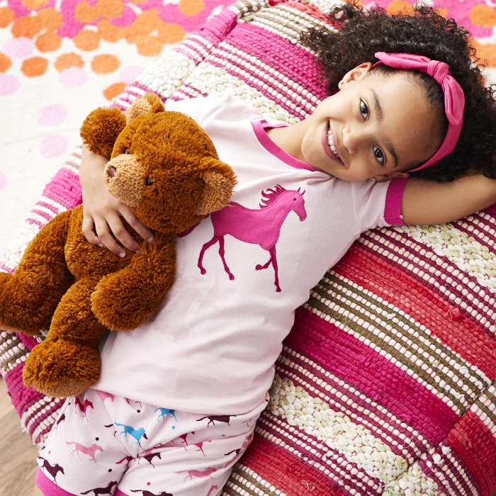 child and stuffed bear relaxing on pillow