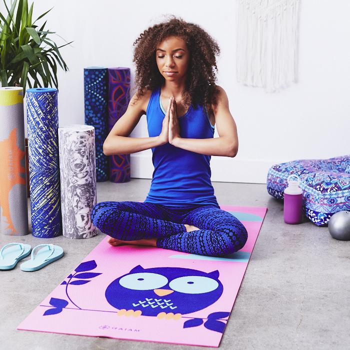 woman seated on yoga mat and meditating