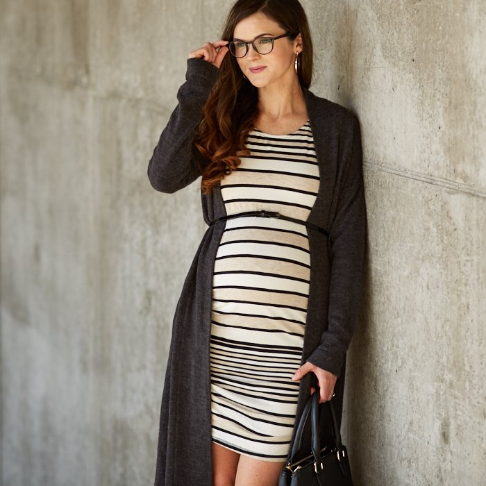 Woman wearing tan-and-black barcode stripe maternity sheath with long, open-front cardigan