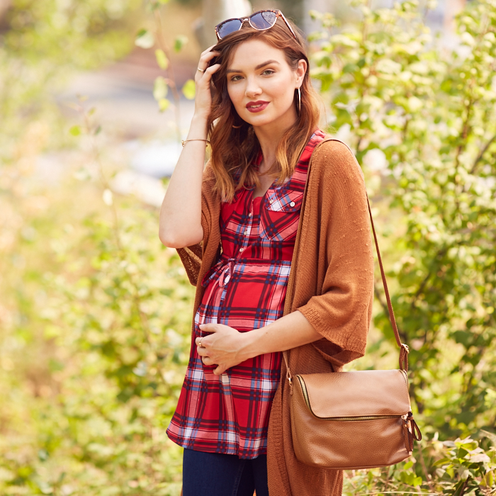 Woman in plaid maternity top with pumpkin-color cardigan and shoulder strap purse