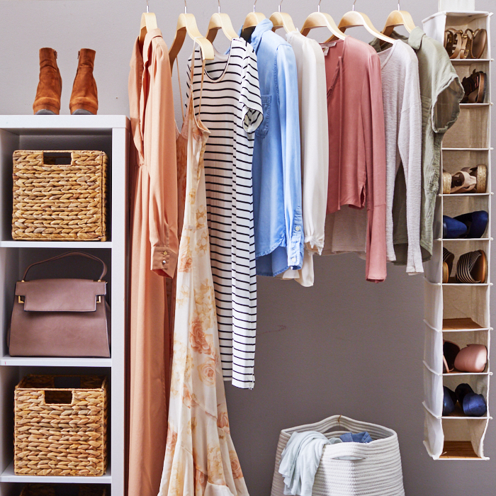 Decluttering example of open closet with hanging clothing, shoe rack, shelves and baskets.