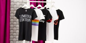 Five graphic tees displayed on a rolling hanger