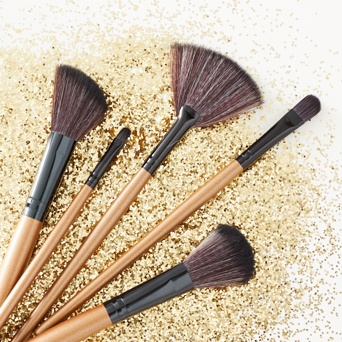 Assortment of makeup brushes on a gold glitter background