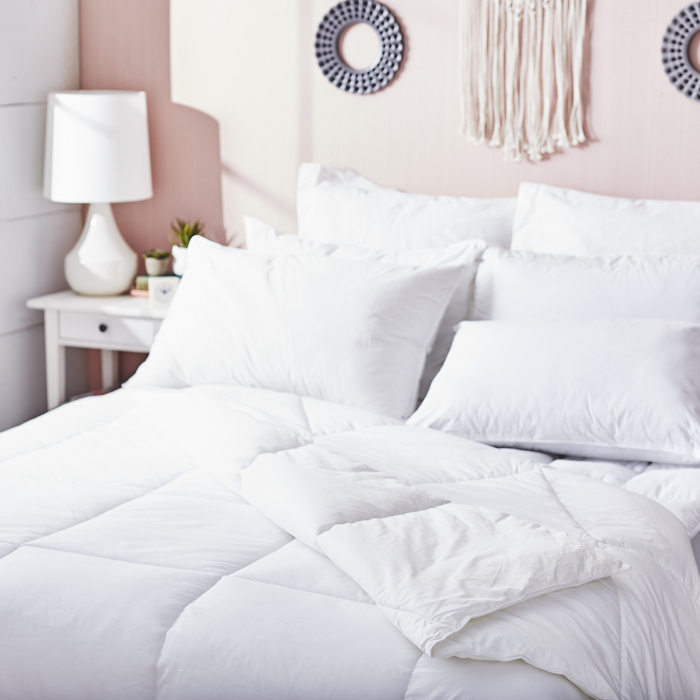 Queen-size bed with white down quilt and multiple pillows