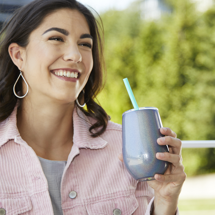 smiling woman outdoors, holding beverage