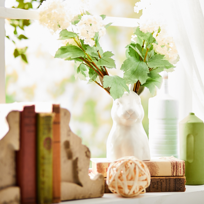 Weathered corbel bookends, rabbit planter with greenery, nature-inspired accents