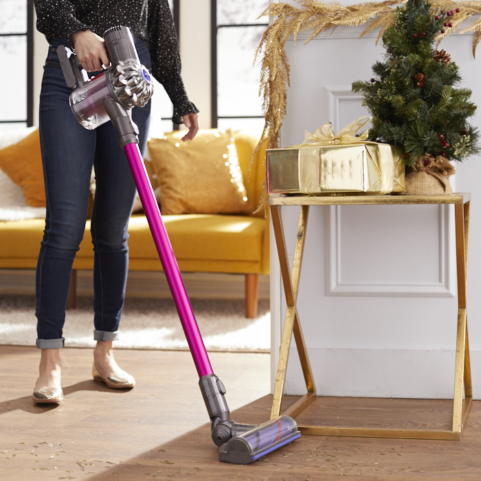 Woman cleaning family room floor with hand-held vacuum