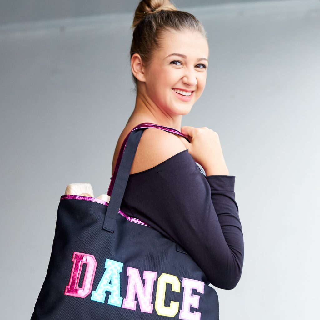 "Young adult ballerina carrying a tote with ""DANCE"" lettering detail"