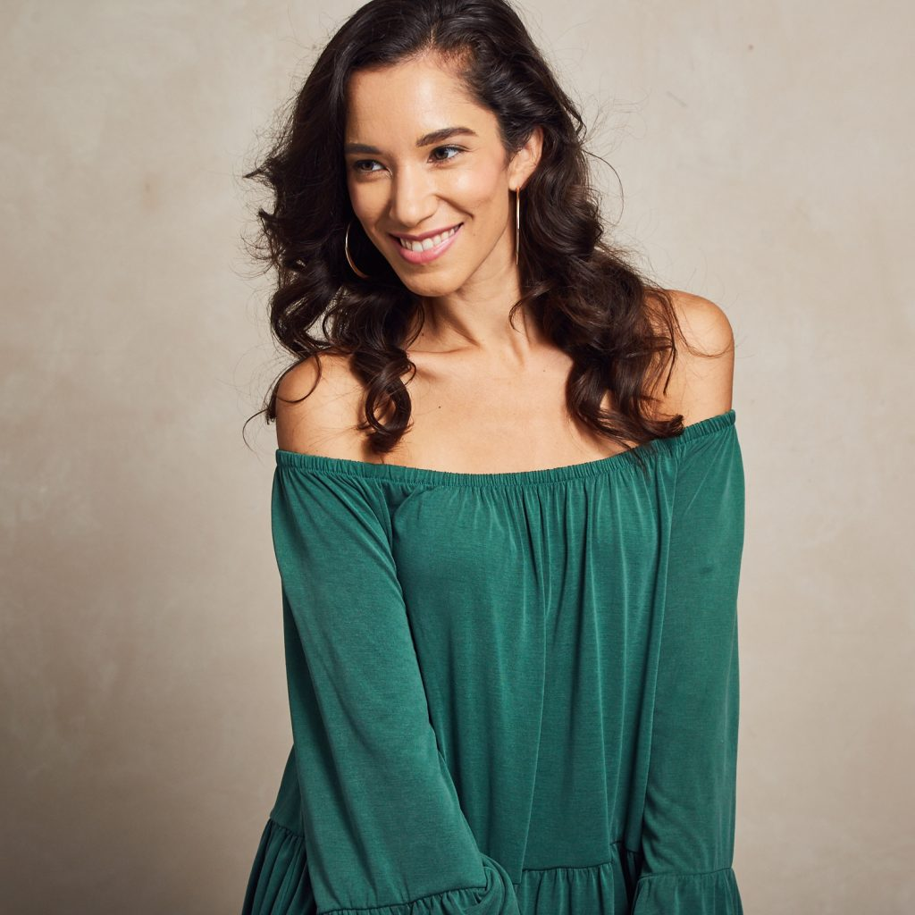 Woman in green off-shoulder top with long brunette curls