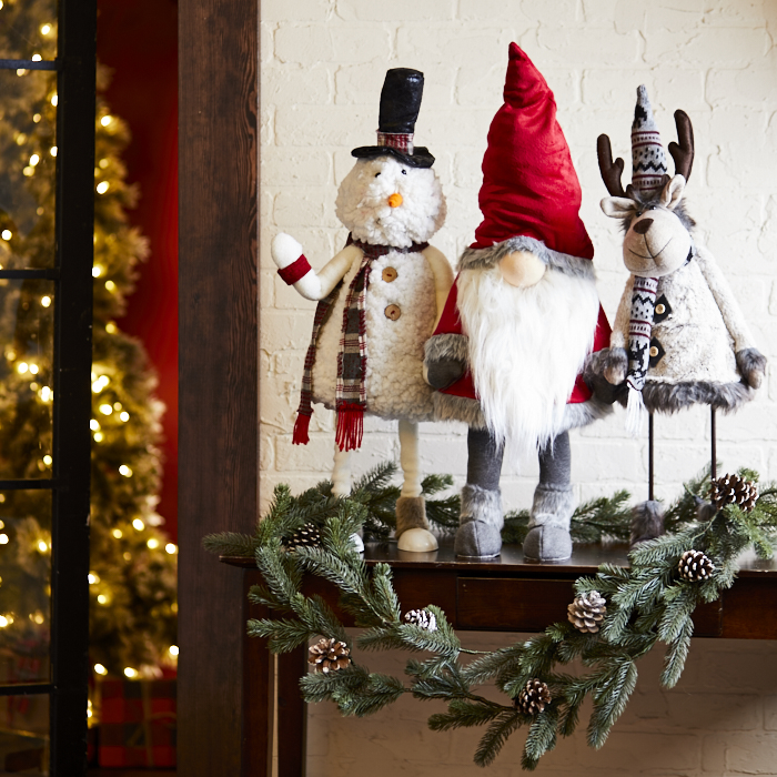 Fireplace mantel decorated with felted snowman, deer and gnome figurines and pine boughs is a great way to decorate a holiday home