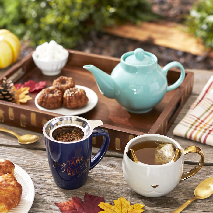 Tray with teapot, teacups, scones and condiments on an outdoor table