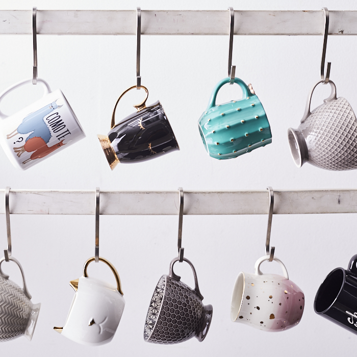 Array of tea mugs hanging from hooks