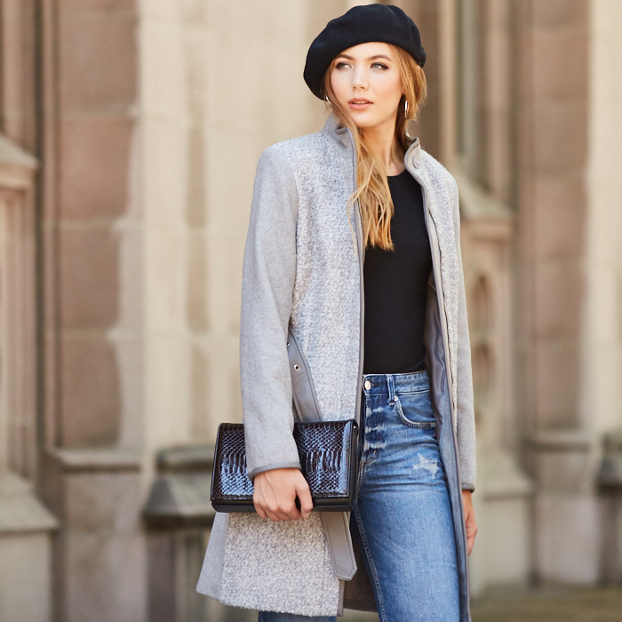 Woman in gray coat and black beret carrying black faux crocodile clutch purse