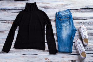 Black top with blue jeans. White canvas shoes and pants. Outfit with high collar top. Female clothing on wooden table. Black top is a great layering piece to bring on a winter vacation.